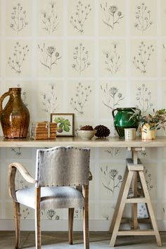 Hand drawn botanical studies of thistles are arranged within an irregular grid on this delicate wallpaper by Sanderson.