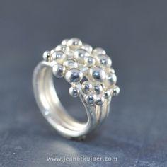 Balletjesring bestaand uit drie ringen die aan de achterzijde aan elkaar zijn gesmeed en aan de voorkant zijn bezaaid met zilveren balletjes is verschillende groottes. De voorzijde van de ring