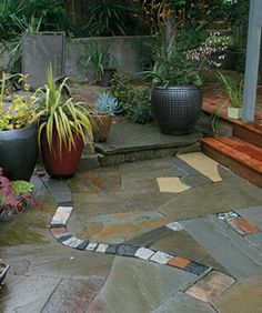 Salvaged pieces of brick, granite cobblestone, and beach stones are used in combination with new bluestone to create this singular patio.