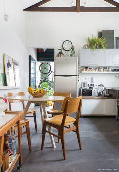 Sala de jantar tem mesa e cadeiras de madeira e piso de cimento queirmado.