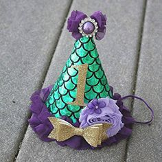 Mermaid first birthday - First Birthday Hat This first birthday party hat is made with a green fish scale fabric. The inside is lined with felt and has an elastic that goes under the childs chin. accented with chiffon ruffles and flowers, topped with a purple rhinestone button. A gold