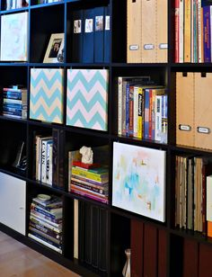 Clean up a bookshelf by adding some hanging canvases with hook and eyes to cover certain cubbies (not everyone needs to see everything on your shelf). And, the art can change. It could even be kids' art