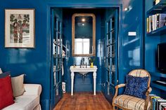 The blueberry lacquer extends to the powder room, whose central feature is an elongated gold leaf Louis Philippe mirror from the 19th century.