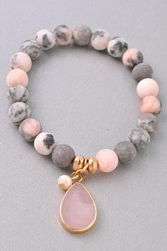 Rose Quartz Semi-Precious Stone Beaded Stretch Bracelet. Gray and pink opaque matte stone beads with a rose quartz drop charm. Due to the nature of natural stones, they may vary in shade.