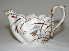 Rare A.A. VANTINE Antique hand painted porcelain Creamer Japan, 1800s. Very beautiful piece of art w/ raised texture hand painted enameled design. This gorgeous creamer depicts a spray of grasses done in gold paint w/ raised beading on the butterflies. Artfully done in a beautiful range of pastel colors w/ mint green, peach, light blue, pale yellow and light rust w/ raised burnished gold accent. The base color is white and the glaze is glossy.  (hva)