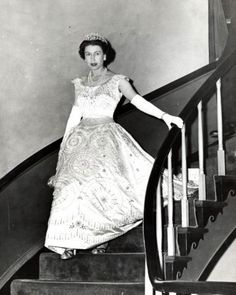 Queen Elizabeth II walking down the stairs in the Williamsburg Inn wearing a Hartnell creation .....
