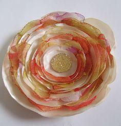Flor com camadas de cetim bege e chiffon predominantemente em tons de salmon.