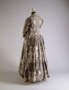 """Painted and Dyed Cotton Chintz Gown, early 18th century The elegant, sweeping line and open robe front are very similar to Indian court robes. Dresses made from Indian chintz called """"wentke"""" became popular throughout northern Europe. This gown's somber color pallet suggests it may be a mourning gown."""