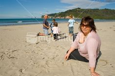 Mother looking with children and father playing in background