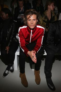 Dougie Poynter attends the Sibling show, wearing suede cowboy boots and a sporty red zip-up.