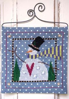 Snow Magical is the title of this cross stitch kit that includes the pattern, wire hanger and button pack. You supply the threads (Weeks Dye Works Daffodil, Daylily, Envy, Oak, Onyx, Peoria Purple, Romance, Swiss Chocolate and Whitewash) or DMC threads.