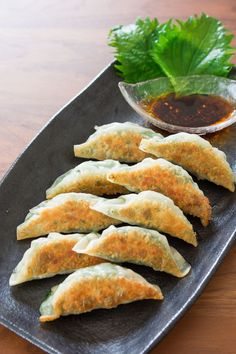 Crisp on the bottom, tender on top, these pork and garlic chive gyoza (餃子) are wrapped with green shiso for a tasty twist on classic Japanese potstickers. Perfect for Super Bowl Sunday! Japanese Dishes, Japanese Food, Japanese Recipes, Shiso Recipe, Asian Appetizers, Asian Snacks, Yummy Food, Tasty, Asian Cooking