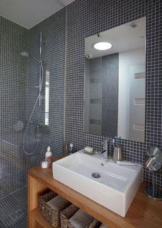 Et pourquoi pas la mosaïque pour mettre en valeur la salle de bains de votre maison alliance construction, ici on opte pour un gris moderne rehaussé par un mobilier en bois.