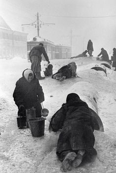 Civilians fetching water from a broken water pipe in the besieged city of Leningrad, Soviet Union - January 1942.