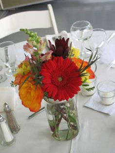 These fall designs feature mini gerberas, yellow ranunculus, two-tone yellow & red roses, burgundy scabiosa and green hypericum berries.  Mason jars create an easy, casual style for the centerpieces.