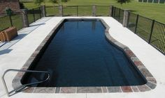 An outback Blue Color Moroccan Style fiberglass pool with Natural Stone coping and white concrete.