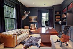 awesome man office - love the Chesterfield sofa, dark walls and cabinetry, and liberal use of taxidermy!