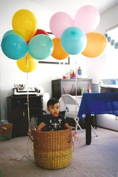 toddler in basket with balloons photo