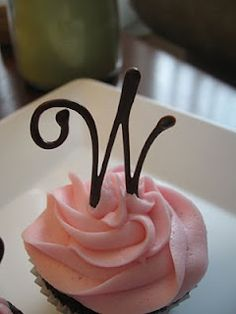 Chocolate cupcake with buttercream frosting and a chocolate monogram letter.  The letter is delicate and beautiful.  The monogram was made by melting chocolate and piping it onto parchment paper until it hardens.