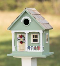 Welcome songbirds to your yard with this Spring Cottage Birdhouse, adorned with cheerful color, front porch, hanging rugs and a floral wreath.This wooden birdhouse has a pine-shingled roof and a dia. entry hole made for wrens, finches and chick Cool Bird Houses, Decorative Bird Houses, Bird Houses Painted, Fairy Houses, Bird House Plans, Bird House Kits, House Paint Design, Homemade Bird Houses, Bird House Feeder