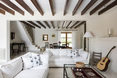 Living Room - A living area with white sofas and exposed beams