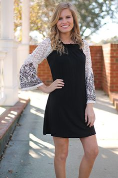 "This dress does black and white oh-so-well! The white lace bell sleeves on this piece are right on trend and we love the black pattern on the bottom of them. The body of the dress is a soft stretchy material that is super comfy. Just add a statement necklace and your favorite shoes!   Fits true to size. Kali is wearing a small.  from shoulder to hem:  small=33""  medium=34  large=35  XL=36"
