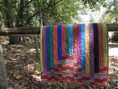 A jelly roll quilt made with Kaffe Fassett stripes and solids - by Needle and Foot.