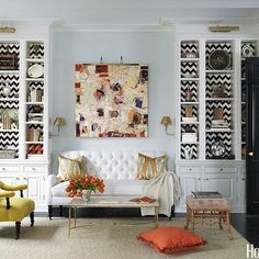 House Beautiful - living rooms - white, built-ins, hand painted, white, brown, chevron, herringbone, pattern, back, shelves, flanking, Lee Industries, white, tufted, loveseat, custom, shade, robin's egg blue, walls, brass, sconces, gold, silver, ikat, pillows, black, doors, built-in cabinets, built-ins, living room built-ins, white built-ins, white built-in cabinets, built-in bookcase, living room bookcase, lined built-ins, lined built-in cabinets, lined built in bookcase, floor to ceiling…
