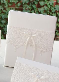 Vintage Lace Wedding Memory Book covered in satin that is available in white or ivory. The cover features an intricate lace overlay that has a scalloped bottom edge. The center of the front cover is decorated with a matching satin button and a satin ribbon bow with two long tails. Inside, the memory book has a 3-ring brass binder with elegant embossed pages to record all your favorite memories from the proposal to your honeymoon.