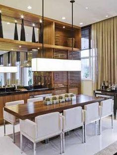 a cozinha fica escondida atrás das portas ripadas que    transformando o ambiente em uma sala de jantar.