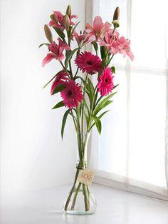 Claudine: Arreglo de astromelias y gerberas rosadas en un delicado florero de vidrio.