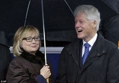 Hillary holding umbrella over both her and Bill  after Terry McAuliffe's inauguration - January 11, 2014.