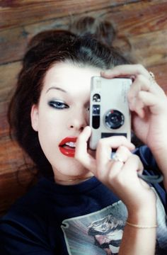 Milla Jovovich with point and shoot by Chris Floyd~UPDATE - Camera model is apparently a Contax T2 - I couldn't identify it. Cheers to http://redfishingboat.tumblr.com for the heads up!