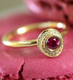 Andrew Geoghegan Clair de Lune ruby engagement ring, surrounded by waves of white diamonds and pink sapphires and set in yellow gold. Propsal idea? Presented on a purple pink magenta macaroon. http://www.thejewelleryeditor.com/bridal/article/sapphire-engagement-rings-number-one-coloured-gem/ #wedding