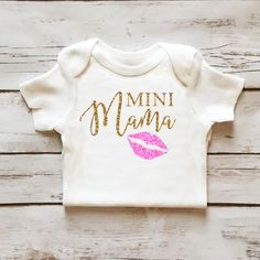 Mini Mama Sparkle Onesie in Gold and Pink Glitter perfect for baby girl. Browse the entire collection at www.shopcassidyscloset.com