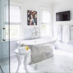 Chic bathroom features a cast iron tub and an Arteriors Lola Side Table placed atop a carrera marble herringbone tiled floor flanked by windows dressed in pinstripe roman shades next to a flatscreen TV mounted on the wall. Ceramic Tile Floor Bathroom, Bathroom Flooring, Bathroom Wall, Interior Design Photos, Luxury Interior Design, Interior Paint, Marble Herringbone Tile, Carrara Marble, Herringbone Pattern