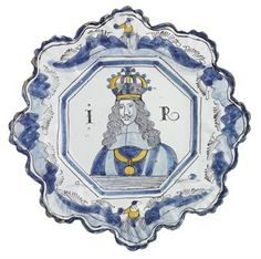 A BRISLINGTON DELFT POLYCHROME ROYAL PORTRAIT MOULDED PLATE OF JAMES II  CIRCA 1685  The centre painted in two tones of blue, ochre and manganese with a half-length portrait of James II flanked by the initials IR within an octagonal well, the foliate moulded lobed border with two chinoiserie figures among blue rockwork and manganese grasses  9¼ in. (23.5 cm.) wide