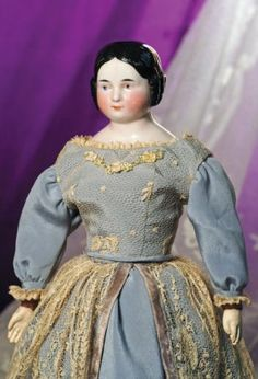 """CHINA DOLL WITH COVERED-WAGON HAIR STYLE. 17"""". Pink-toned china shoulderhead with smooth black center-parted hair and ringlet curls, painted features, blue eyes, red and black lid lines, tapered brows, closed mouth, original Lackman cloth body with composition hands, blue silk and ivory lace gown. Commentary: Very nice quality porcelain and facial painting, good original body, hands repainted, light paint wear on tip of nose and left cheek."""