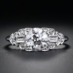 1.02 Carat Diamond Platinum Art Deco Diamond Engagement Ring. A high-color, one-carat (plus .02) European-cut diamond shines mightily from this stunning original Art Deco ring, crafted in platinum, with a distinctive shoulder design comprised of baguette and small round diamonds. A sleek knife-edge finish all around the ring shank completes this superb vintage engagement ring from the 1920s-30s. Via Lang Antique & Estate Jewelry.