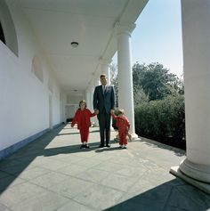 1963. 28 Mars. President John F. Kennedy poses with his children, Caroline Kennedy and John F. Kennedy, Jr., in the West Wing Colonnade of the White House, Washington, D.C.