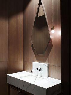 Banheiro com revestimento de madeira e pia em Mármore