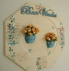 Um enfeite lindo para decorar a entrada da sua casa e dar as boas vindas às suas visitas! Placa em mdf na cor palha com pintura decorativa de tijolos, folhas e gaiolinhas. Com apliques de pérolas, palavra bem vindos em mdf e vasinhos em resina pintados com arranjinhos de mini rosas. Peça toda encerada. Medidas: 35cm x 35cm R$ 90,00