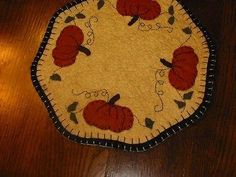 "Primitive Candle Mat - Pumpkins  9"" dia. This is a new handcrafted/handsewn candle mat. The backing has a blanket stitch to a tea dyed cream top.  I have sewn"