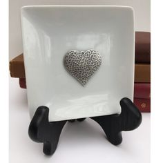 "Our trinket tray dish features a silver hammered heart. The trinket tray is 4.5 inches x 4.5 inches. The silver hammered heart measures 1.50 inches x 1.50 inches. The trinket tray dish comes individually boxed in a white gift box. Trinket trays are perfect to collect ""trinkets"" or coins from your desk or dresser. They also make an artistic statement tucked beside books on a bookshelf. White Gift Boxes, Hammered Silver, Valentine Gifts, Bookshelves, Trays, Dishes, Dresser, Coins, Desk"