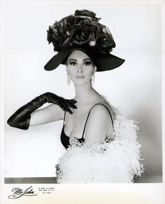 This photograph is one of three promotional photographic prints and the front cover of booklet for Mr John's Exciting Boldini collection for autumn and winter 1964. It shows a model wearing a silk hat decorated with large silk roses, called L'Imperatrice, (The Empress).