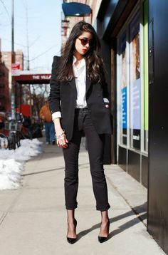 White button-down, black blazer, black tights worn under black skinny jeans, and black pumps