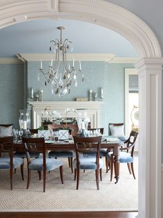 Viewed through the elliptical arch at the entry hall, the blue dining room has a classically designed fireplace and ceiling cornice. @dvharchitects