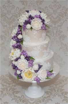 Brush embroidered lace wedding cake with cascading sugar peonies, lilac sugar flowers and berries.