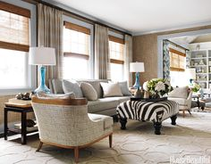 Textures and patterns in the living room all work together because they share the same neutral palette. Hickory Chair's Monroe sofa, Tomlinson/ Erwin-Lambeth armchairs covered in Pierre Frey's Lafayette, and a vintage ottoman are set off by ABC Carpet & Home's Honeycomb rug. Trim painted in Benjamin Moore's Harbor Haze picks up the blue of the Murano lamps. Walls in Phillip Jeffries's Driftwood grass cloth. Curtains in Lulu DK's Tuscany.   - HouseBeautiful.com