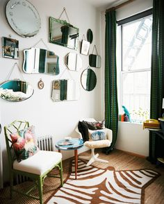 Eclectic Vintage Living Room: A grouping of mirrors hung above a room with a zebra-print rug and green patterned curtains.